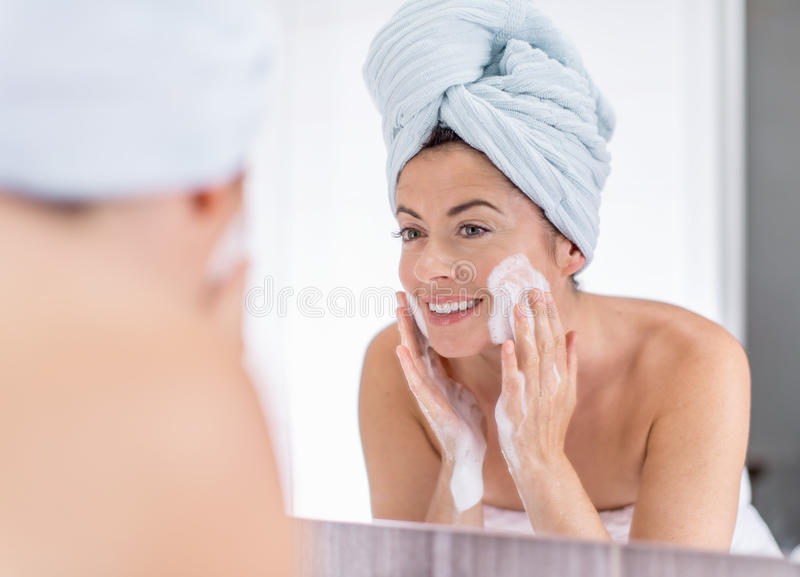 Middle aged woman cleaning her sking over the sink stock photo
