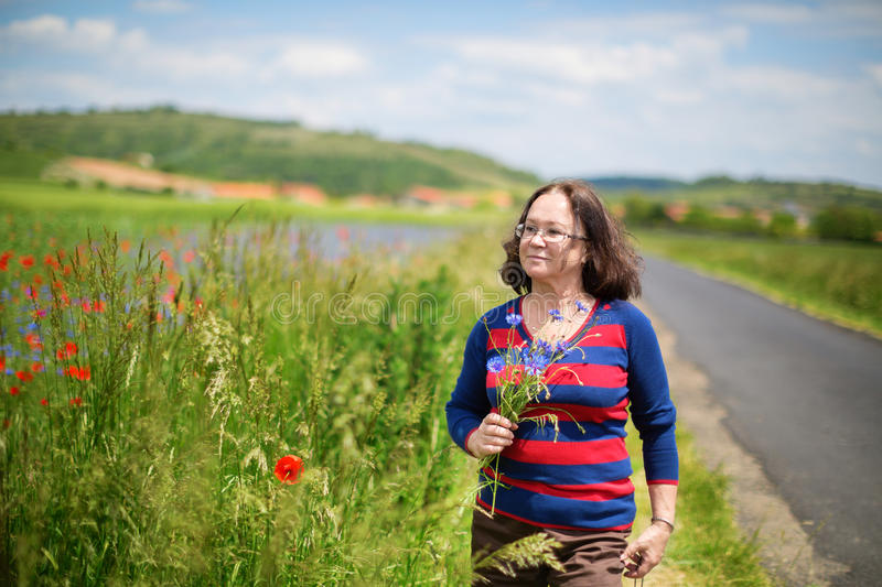 Middle aged woman with cornflowers and poppies. Beautiful middle aged woman with cornflowers and poppies outdoors royalty free stock image