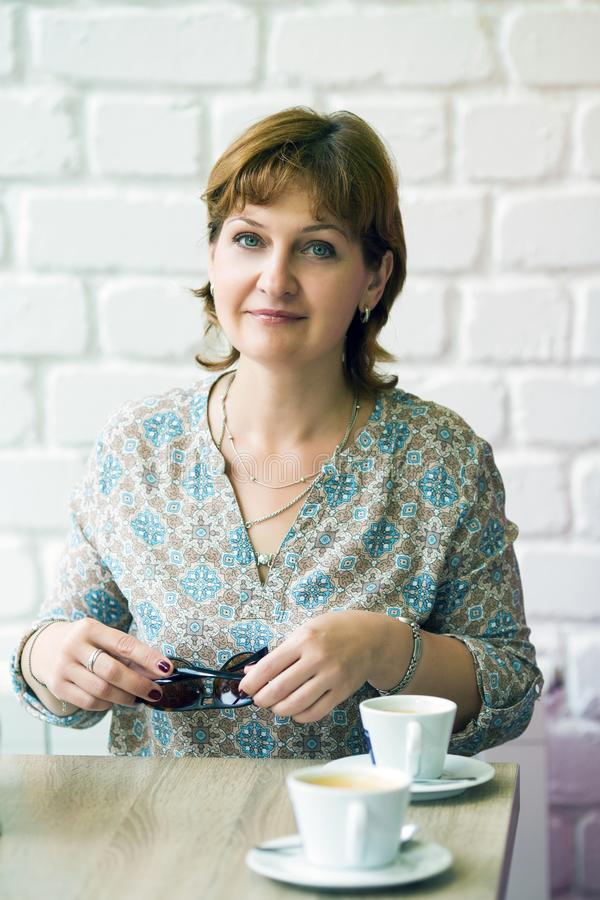 Middle-aged woman with a cup of coffee. At a table in a cafe royalty free stock photography