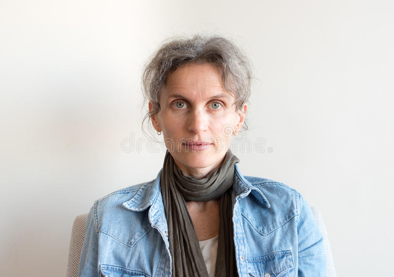 Middle aged woman in denim shirt. Portrait of middle aged woman with grey hair, denim shirt and scarf stock image
