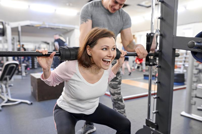 Middle-aged woman doing sports exercise in fitness center. Personal gym trainer assisting mature woman. Health fitness sport age stock images