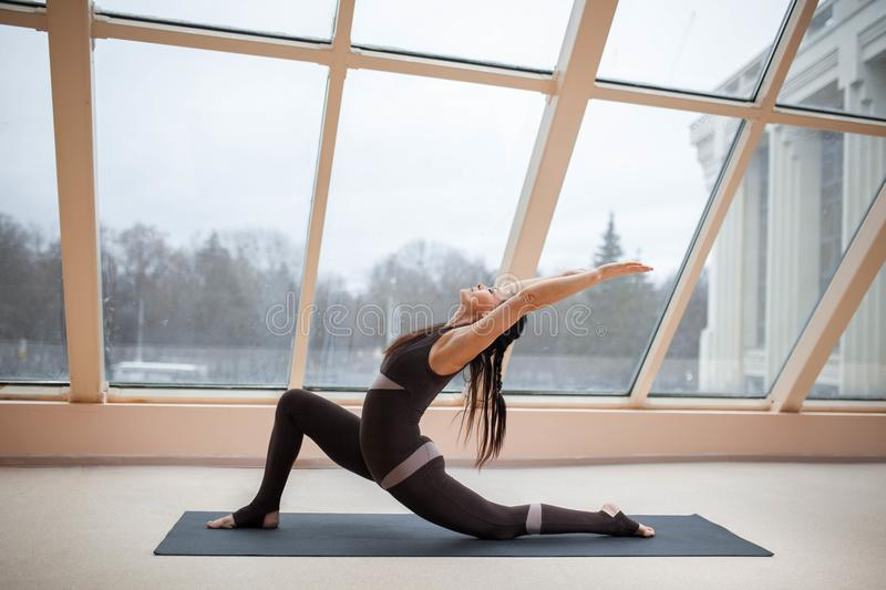 Middle aged woman doing yoga Horse rider exercise, anjaneyasana pose on the mat in front of large windows., exercise fitness, spor royalty free stock images