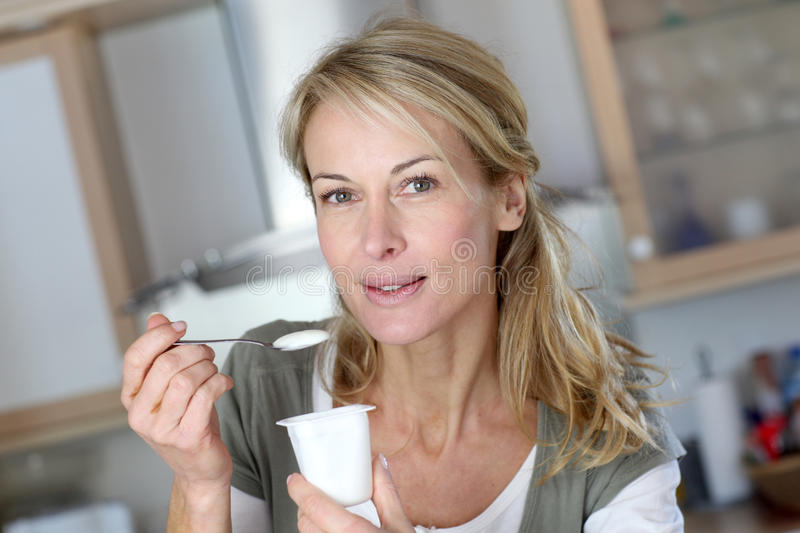 Middle-aged woman eating yoghurt stock photos