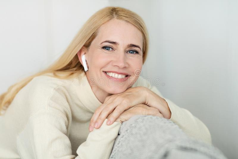 Middle-aged woman enjoying music in airpods, smiling to camera royalty free stock image