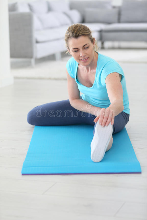 Middle-aged woman excercising and stretching stock photo