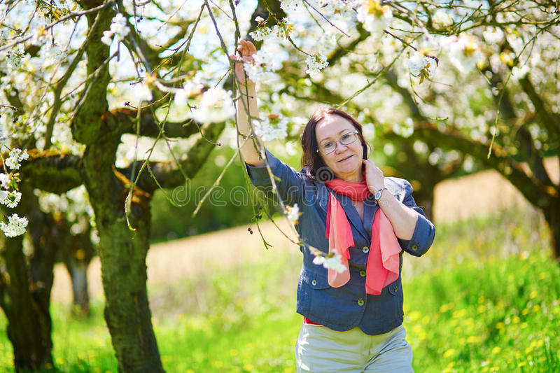 Middle aged woman in garden on a spring day. Beautiful middle aged woman in garden on a spring day stock image