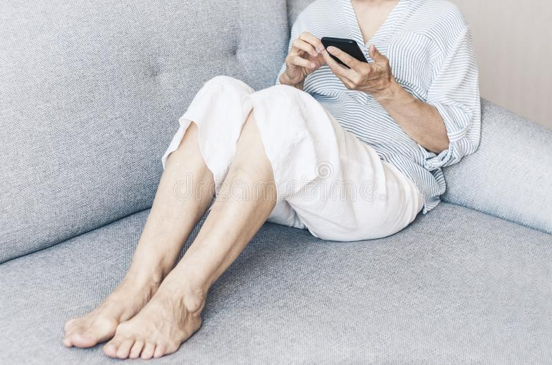 Middle-aged woman on the gray sofa use smartphone stock photography