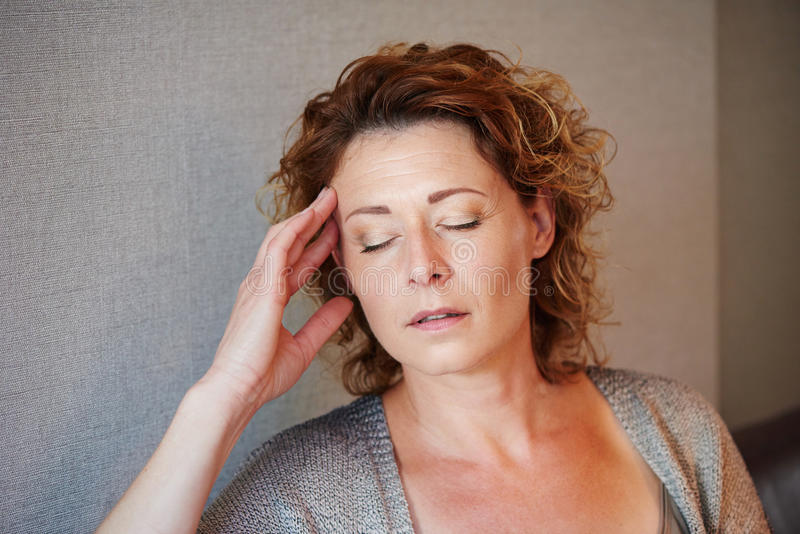 Middle aged woman with hand to head in pain stock image