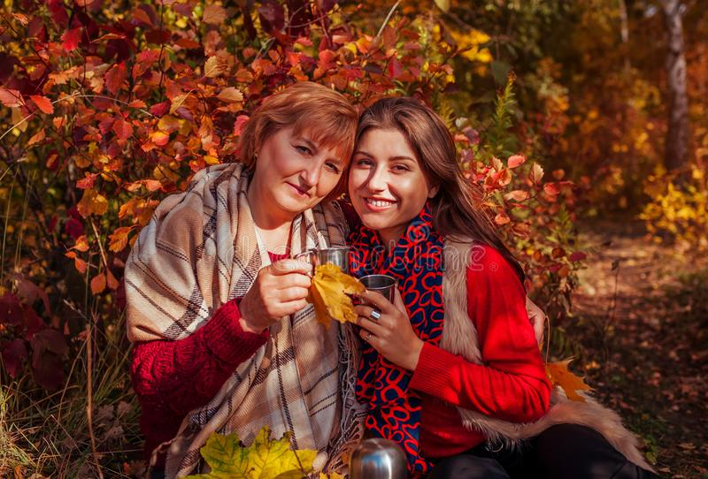 Middle-aged woman and her daughter having tea in the forest stock image