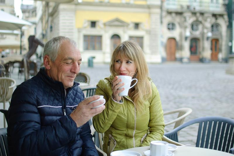 Middle-aged woman and her elderly husband spending time together outdoors sitting in cafe with terrace outdoors and royalty free stock images