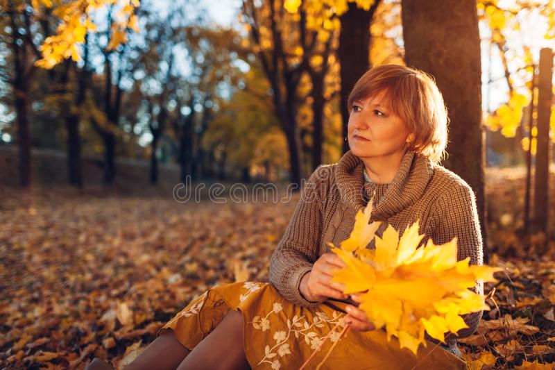Middle-aged woman holding bouquet of maple leaves. Lady enjoying autumn nature and relaxing. Sitting on the ground royalty free stock photo