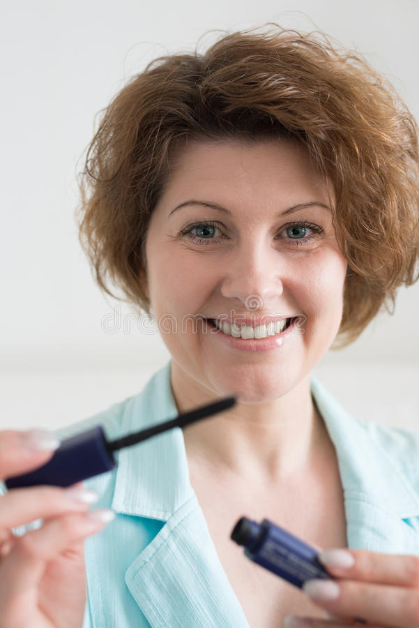 Middle-aged woman holding a mascara in hands of stock photography