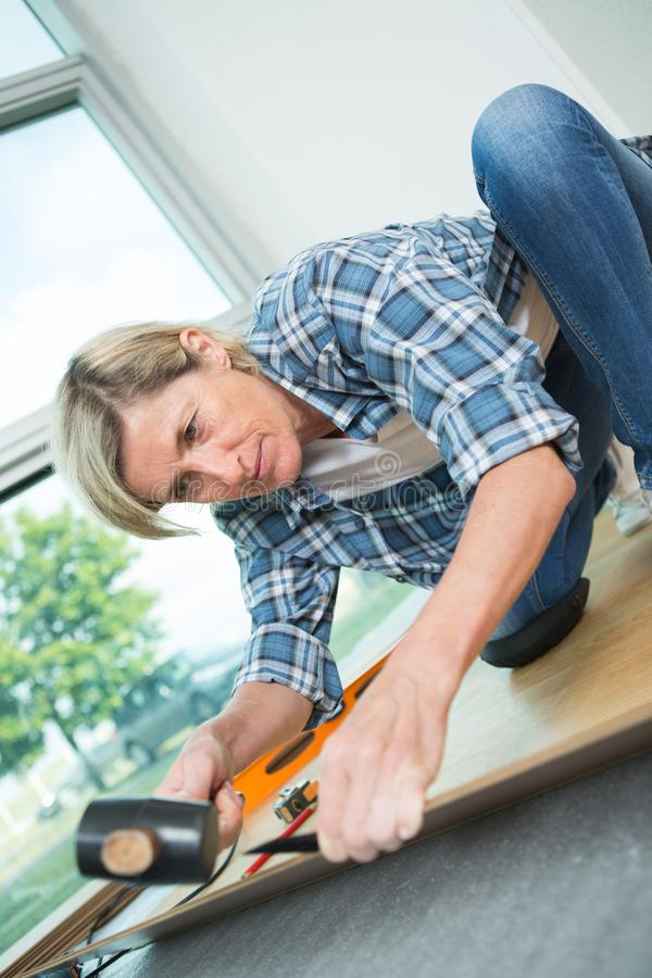 Middle aged woman installing wooden floor stock photos