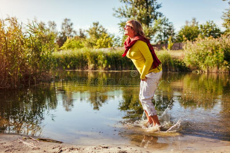 Middle-aged woman jumping on river bank on autumn day. Happy senior lady having fun walking in the forest royalty free stock photo