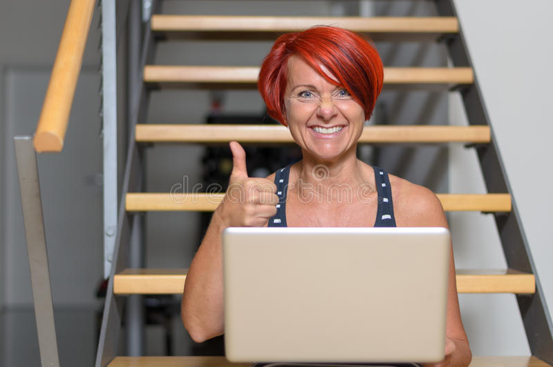 Middle Aged Woman with Laptop Showing Thumbs Up. Happy Middle Aged Redhead Woman with Laptop Computer, Sitting on the Stairs and Showing Thumbs Up Hand Sign at royalty free stock photos