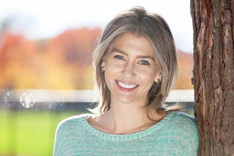 Middle aged woman leaning on tree royalty free stock photos
