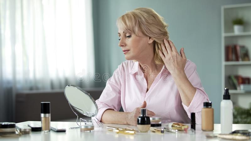 Middle-aged woman looking in mirror at face after skin rejuvenation procedure. Stock photo royalty free stock photos