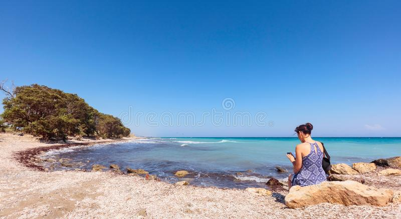 Middle-aged woman with mobile phone on the Mediterranean coast. stock photos