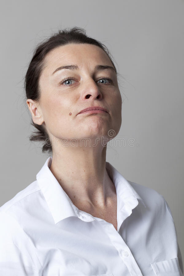 Middle aged woman with mole posing with chin up for arrogance. Attitude concept - beautiful middle aged woman with a mole posing with chin up for arrogance or stock photography