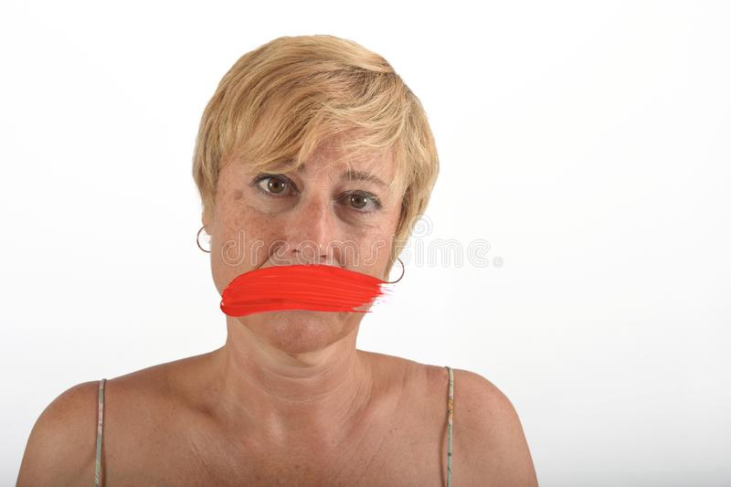 Middle aged woman with mouth covered on white stock photo