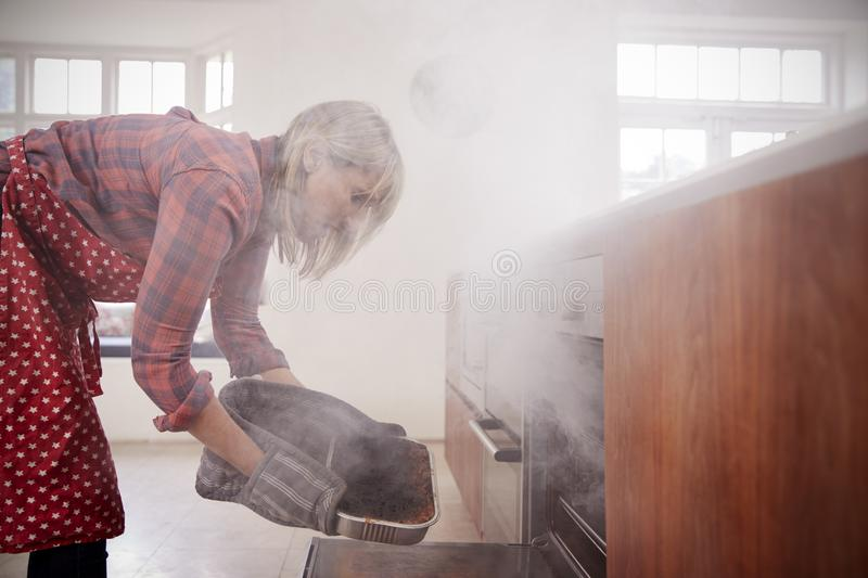 Middle aged woman opening smoke filled oven in the kitchen royalty free stock photos