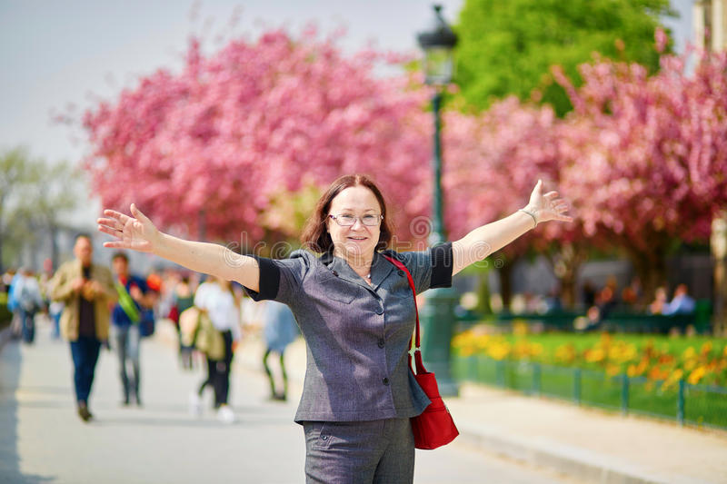 Middle aged woman in Paris. Middle aged woman walking in Paris on a spring day with cherry blossoms in full bloom royalty free stock photos