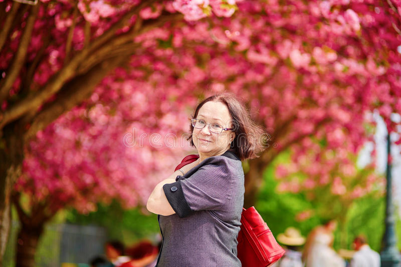 Middle aged woman in Paris. Middle aged woman walking in Paris on a spring day with cherry blossoms in full bloom royalty free stock image