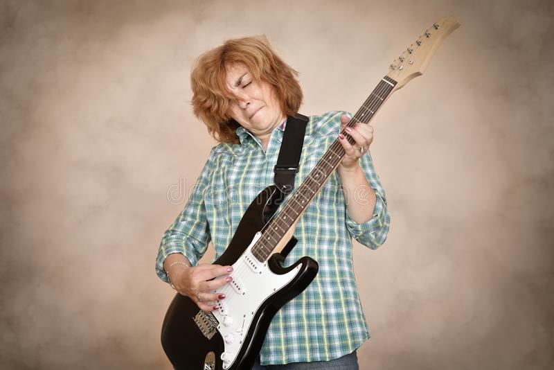 Middle aged woman playing electric guitar royalty free stock images