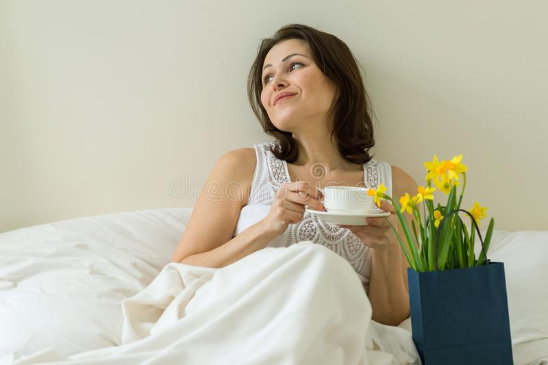 Middle aged woman is pleased with gift, bouquet of flowers royalty free stock photos
