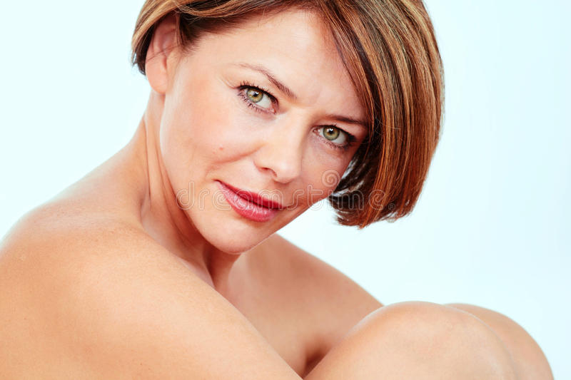 Middle aged woman portrait. Close up portrait of beautiful nude mature woman hugging her knees stock image
