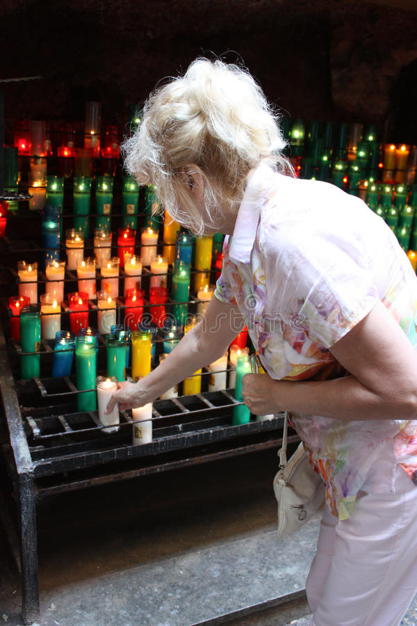 Middle-aged woman puts a candle in Holy place royalty free stock photo