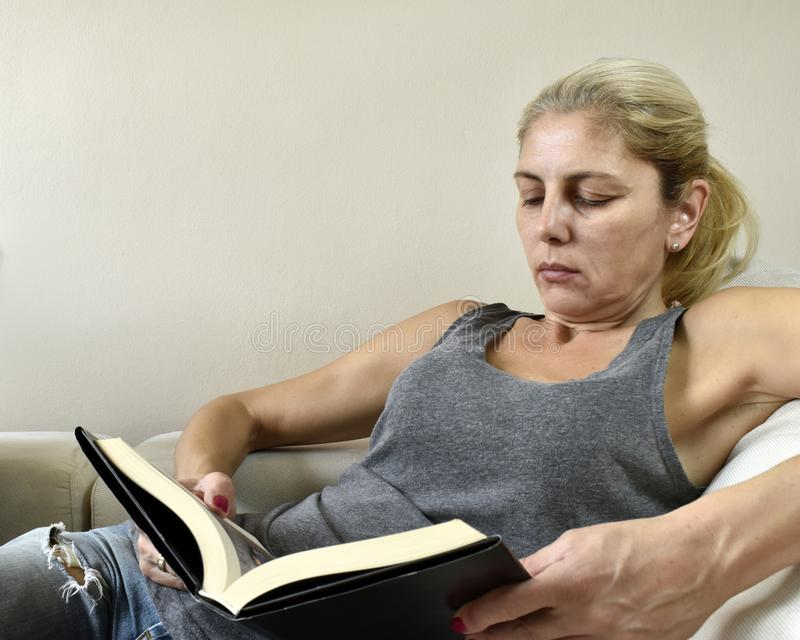 Woman reading book on sofa royalty free stock image