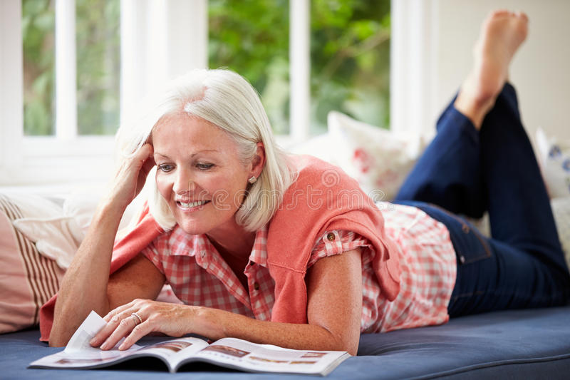 Middle Aged Woman Reading Magazine Lying On Sofa royalty free stock image