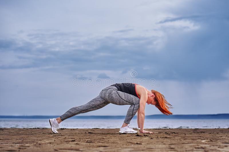 A middle-aged woman with red hair does gymnastics on the sandy shore of a large river. Cloudy spring morning stock photos