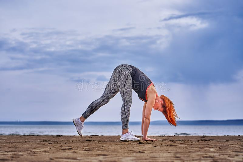 A middle-aged woman with red hair does gymnastics on the sandy shore of a large river. Cloudy spring morning stock image