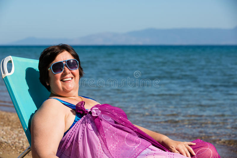 Middle-aged woman resting on the sea royalty free stock photography