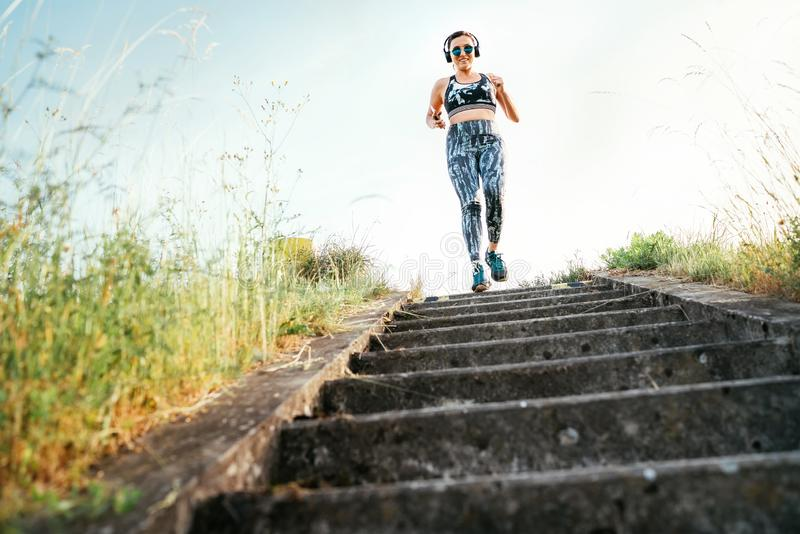 Middle-aged woman running downstairs and listening to music using wireless headphones and smartphone. Morning outdoor run training. Concept image stock photography