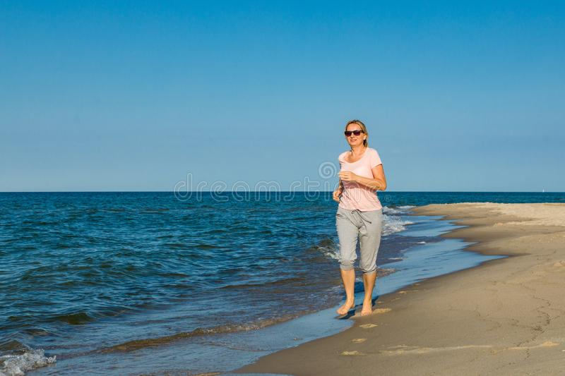 Middle-aged woman running on beach. Middle-aged woman running, jumping on beach stock photo