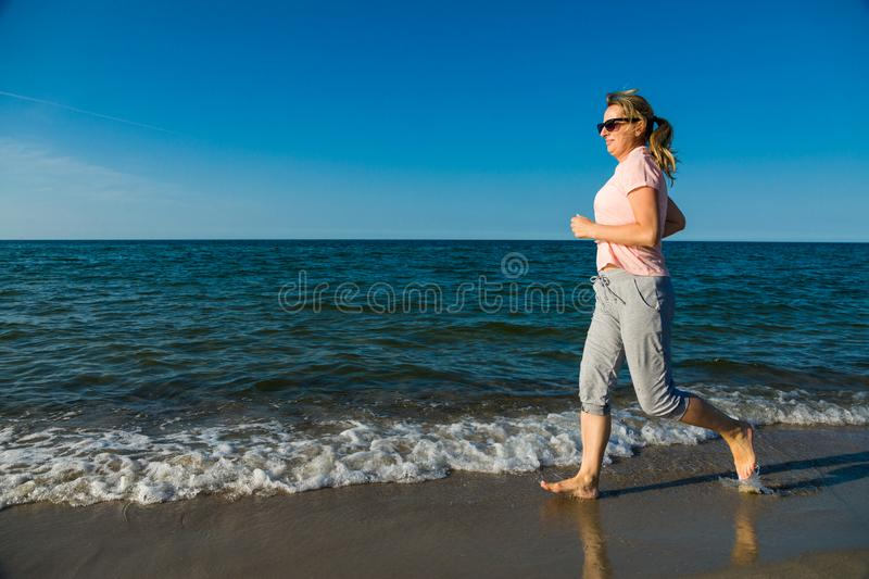 Middle-aged woman running on beach. Middle-aged woman running, jumping on beach stock photos