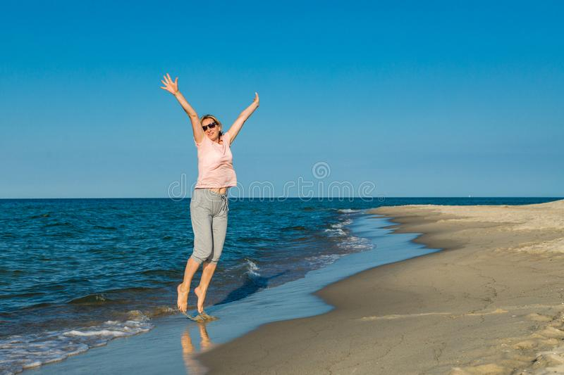 Middle-aged woman running on beach. Middle-aged woman running, jumping on beach royalty free stock photo