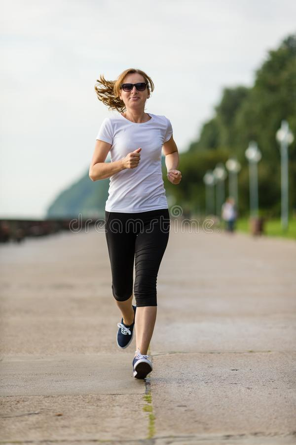 Middle-aged woman running royalty free stock photo