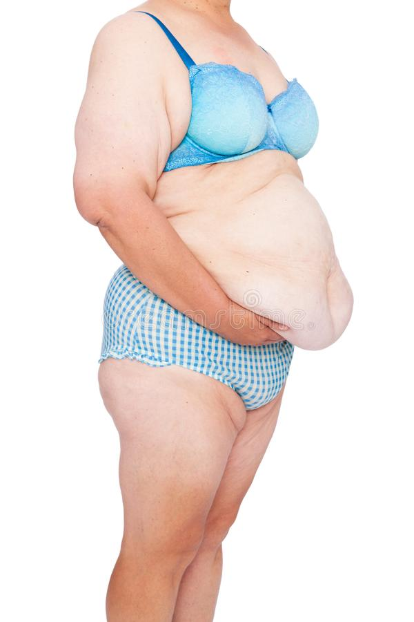 Middle aged woman with sagging skin after babies and extreme weight loss. 45 deg view holding excess belly skin. Middle aged woman with sagging skin after stock photos