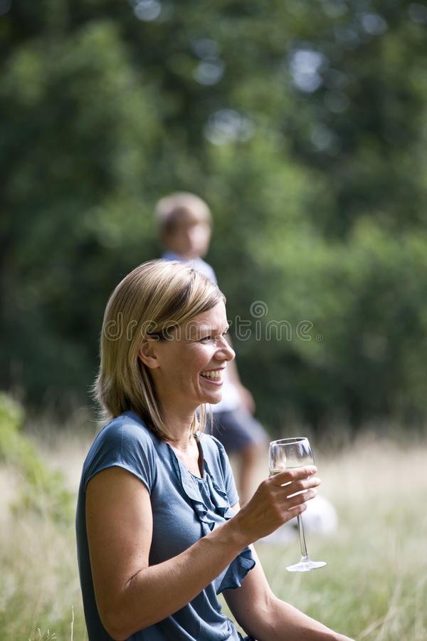 A middle aged woman sitting on the grass, having a glass of wine. A middle aged women sitting on the grass, having a glass of wine stock images