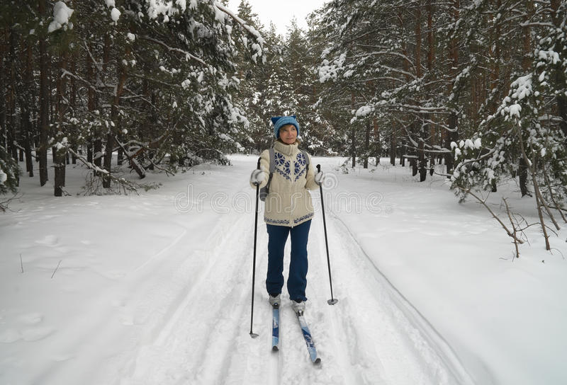 Middle-aged woman skiing. Woman skiing in winter forest royalty free stock image