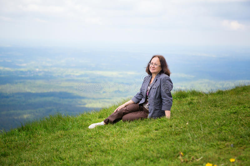 Middle aged woman on the slope of volcano. Relaxed middle aged woman sitting on the slope of volcano in Auvergne, France royalty free stock photo