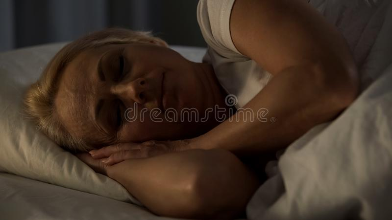 Middle-aged woman smiling sleeping in bed, feeling calm and bliss, night rest royalty free stock image