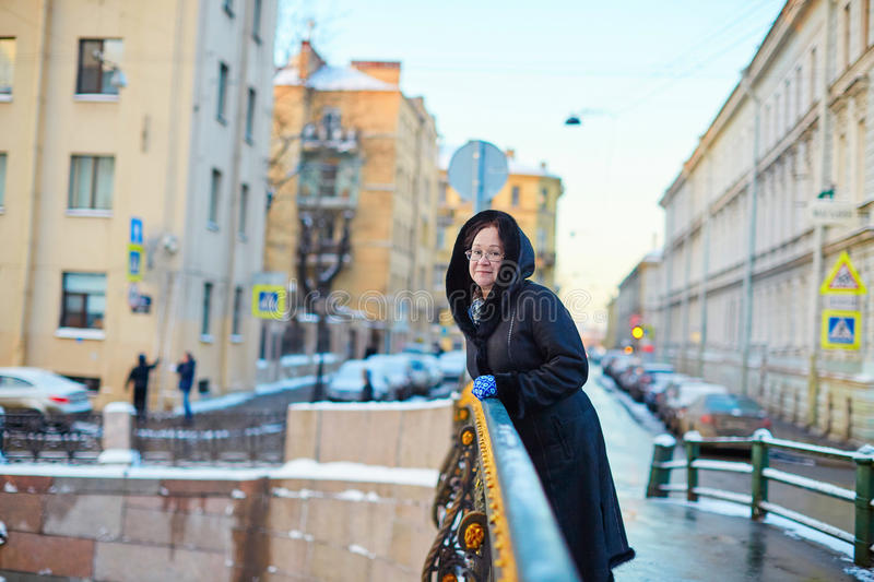 Middle aged woman in St. Petersburg. Beautiful middle aged woman on Moika embankment in St. Petersburg, Russia royalty free stock images