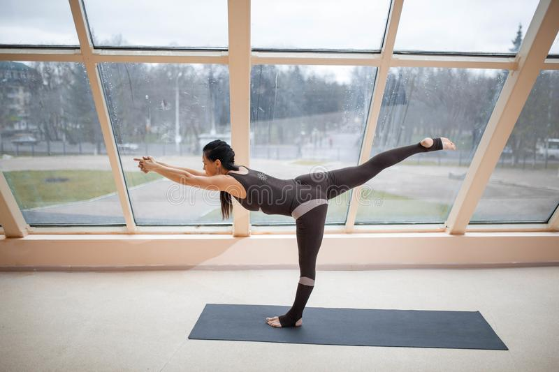 Middle aged woman standing in Warrior three exercise, Virabhadrasana III pose on the mat in front of large windows., exercise fitn stock photography