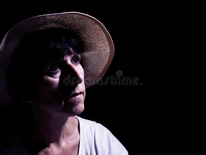 Middle aged woman in straw hat, wistful. Filtered, colored image. stock photos
