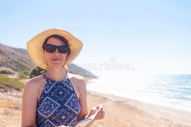 Middle-aged woman with sunglasses and a hat on the Mediterranean stock photography